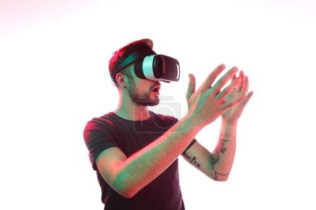 Photo pour Jeune homme en lunettes VR regardant les mains avec une expression de visage choquée tout en se tenant sur fond blanc et explorer la réalité virtuelle - image libre de droit