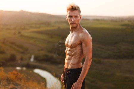 Photo pour Vue latérale du sportif musclé torse nu en short noir debout au soleil sur fond de vallée verte - image libre de droit