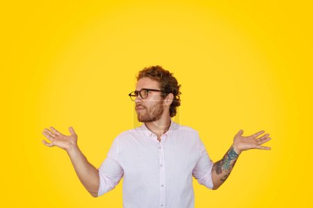 Photo for Handsome young guy in white shirt and stylish glasses gesturing with both hands and looking away in bewilderment while standing on vivid yellow background - Royalty Free Image