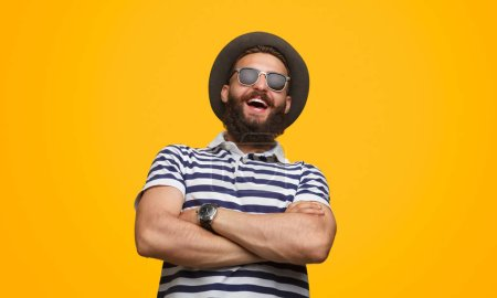 Photo for Handsome bearded male in trendy outfit keeping arms crossed and laughing while standing on bright yellow background - Royalty Free Image
