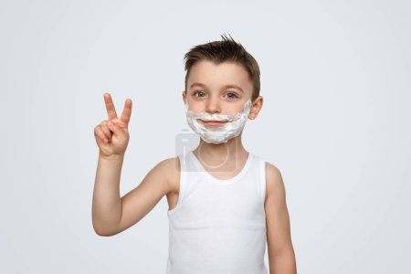 Photo pour Doux petit garçon avec mousse à raser sur le visage montrant deux doigts geste et regardant la caméra tout en se tenant debout sur fond blanc - image libre de droit