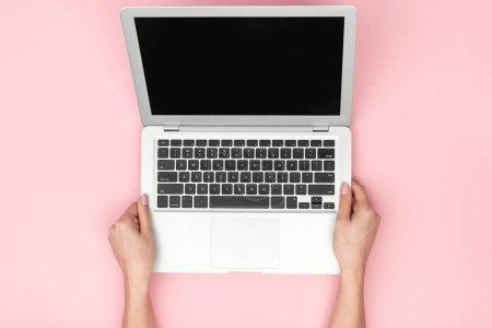 Photo pour Crop femme d'en haut tenant ordinateur portable moderne en argent sur fond rose - image libre de droit