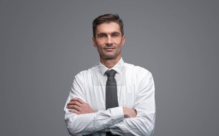 Photo for Positive adult male in elegant shirt and tie keeping arms crossed and looking at camera while standing on gray background - Royalty Free Image