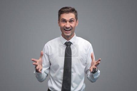Photo pour Attrayant homme adulte en chemise élégante et cravate geste avec les mains et en regardant la caméra avec expression du visage excité tout en se tenant debout sur fond gris - image libre de droit
