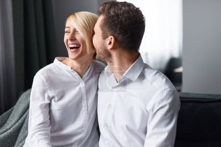 Photo for Excited man and woman embracing and laughing while sitting on comfortable sofa at home together - Royalty Free Image
