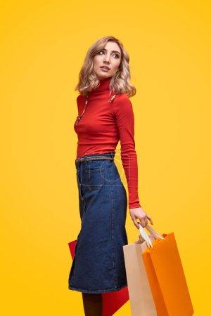 Photo pour Portrait vertical complet du corps de jolie femme en tenue rouge tendance portant des sacs à provisions et regardant par-dessus l'épaule tout en se tenant debout sur fond jaune - image libre de droit
