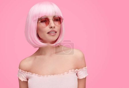 Photo for Beautiful young woman in stylish round sunglasses looking away while standing on pink background - Royalty Free Image