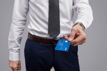 Photo for Closeup shot of a man handing a blue plastic card to camera while standing on gray background - Royalty Free Image