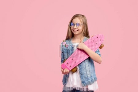 Photo for Adorable girl in trendy casual outfit smiling and hugging skateboard while standing against pink background on weekend - Royalty Free Image