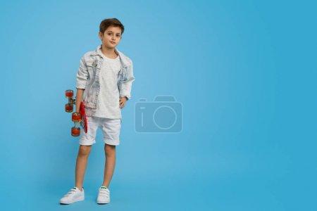 Photo pour Jeune positif avec le longboard rouge moderne regardant l'appareil-photo tout en restant sur le fond bleu vide - image libre de droit