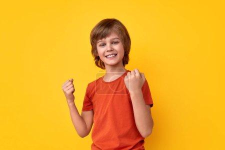 Photo pour Joyeux jeune homme en T-shirt orange serrant les poings et souriant tout en célébrant la victoire sur fond jaune vif - image libre de droit