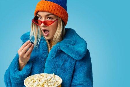 Photo pour Choqué jeune femme en tenue bizarre colorée manger du pop-corn frais tout en regardant le film sur fond bleu - image libre de droit