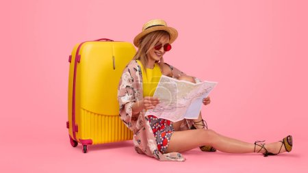 Photo for Happy stylish lady smiling and reading city map while sitting near suitcase during summer vacation against pink background - Royalty Free Image