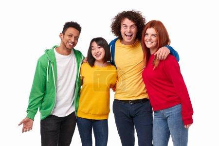 Photo pour Groupe de jeunes gens multiraciaux joyeux dans des tenues colorées vives souriant et regardant la caméra tout en s'embrassant sur fond blanc - image libre de droit
