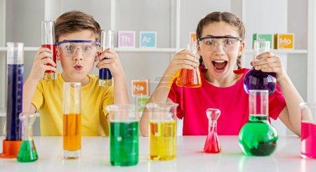 Photo pour Garçon et fille excités avec des flacons de liquides colorés grimacant et regardant la caméra tout en menant des expériences chimiques en laboratoire - image libre de droit
