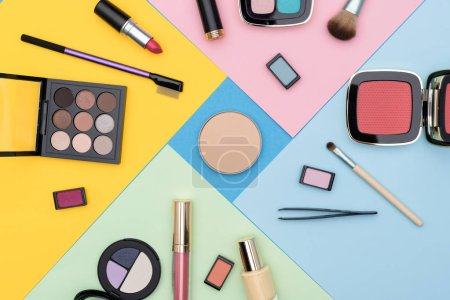 Photo for Set of various makeup tools placed around compact powder against colorful background - Royalty Free Image