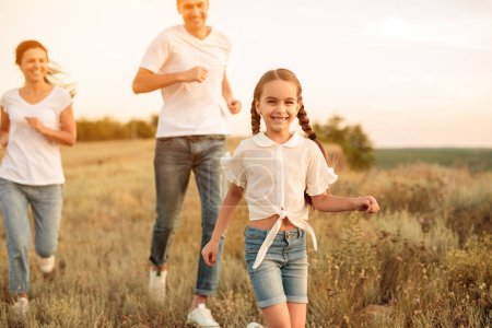 Photo for Adorable happy daughter laughing while running from smiling parents in meadow while spending time in nature together - Royalty Free Image