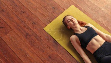 Photo pour D'en haut calme femme en forme relaxant et respirant tout en étant couché à pose de cadavre sur le tapis - image libre de droit