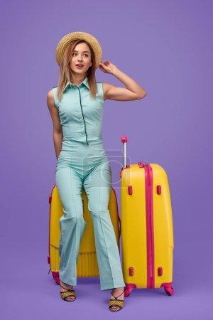 Photo pour Plein corps jeune femme à la mode touchant chapeau et regardant loin tout en étant assis sur la valise pendant les vacances d'été sur fond violet - image libre de droit