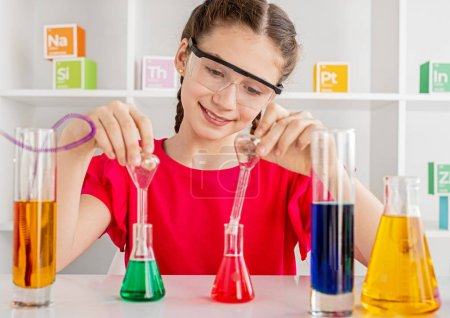 Photo for Cheerful girl with braided hair experimenting with colorful laboratory flasks - Royalty Free Image