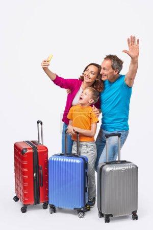 Photo pour Parents joyeux et fils souriant et posant pour selfie tout en se tenant derrière des valises avant le voyage sur fond blanc - image libre de droit