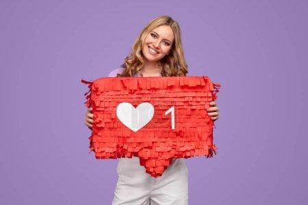 Photo pour Amical jeune femme souriant et montrant bannière avec symbole similaire tout en représentant les médias sociaux sur fond violet - image libre de droit