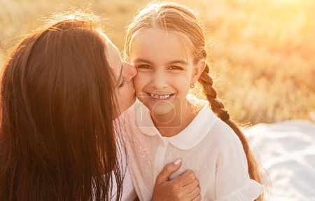 Photo for Cheerful smiling girl with long braids looking at camera while mother embracing and kissing with love on picnic in field in bright sunny day - Royalty Free Image