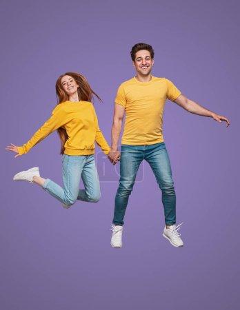 Photo pour Plein corps excité homme et femme en vêtements similaires tenant la main et souriant en sautant et en s'amusant sur fond violet - image libre de droit
