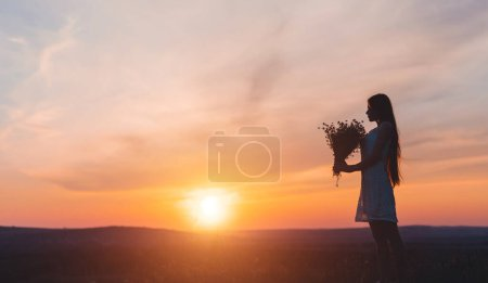 Photo pour Vue latérale de la jeune femelle en robe portant un bouquet de fleurs contre un ciel ensoleillé en soirée d'été dans un champ - image libre de droit