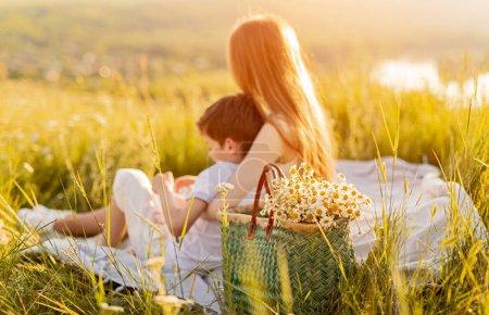 Photo pour Vue latérale d'une sœur anonyme embrassant son petit frère assis sur une couverture près du panier avec des camomilles et se relaxant au coucher du soleil dans la nature - image libre de droit