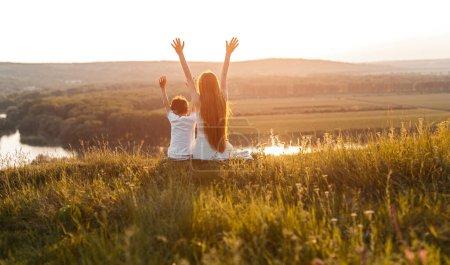 Photo pour Vue arrière de frères et sœurs méconnaissables levant les bras assis sur l'herbe et s'amusant ensemble pendant le coucher du soleil dans la campagne - image libre de droit