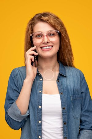 Photo for Positive blond woman in glasses smiling and answering phone call isolated on yellow background - Royalty Free Image