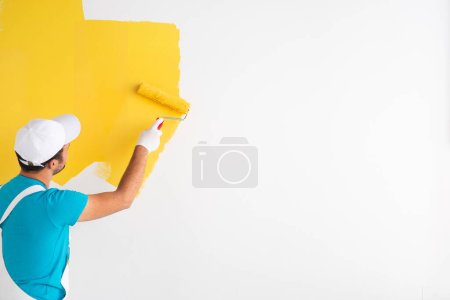 Unrecognizable man painting wall in yellow color