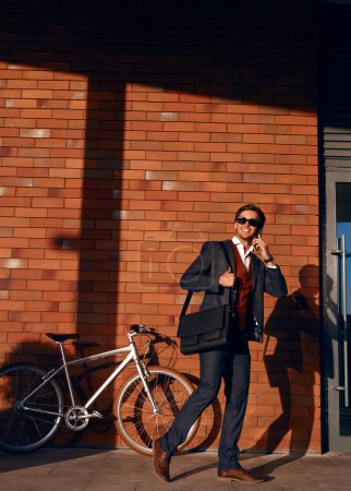 Photo for Full length male entrepreneur smiling and looking away while walking near bicycle and brick building and answering phone call on modern city street - Royalty Free Image