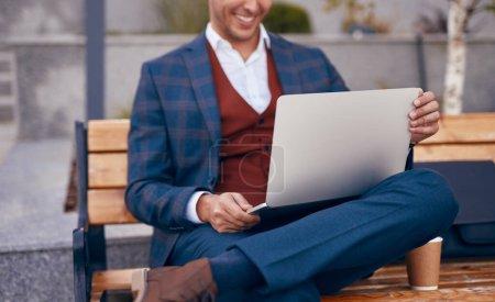 Photo pour Gestionnaire méconnaissable en vêtements décontractés intelligents souriant et lisant les données d'affaires sur ordinateur portable tout en étant assis sur le banc, près de boire pour aller travailler dans la rue de la ville - image libre de droit