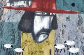 Art of collage with the image of a man in red hat. The technique of authorship using different textures. Shepherd and sheep