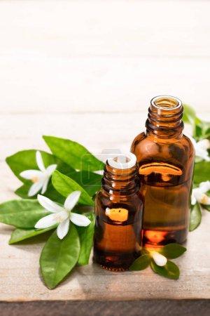 Photo pour Huile essentielle de néroli dans la bouteille de verre brun, avec fleur de néroli blanc frais et feuilles vertes. - image libre de droit