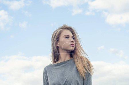 Photo pour Portrait d'une belle fille sur le fond de ciel. Regarde vers la droite. Culture de la jeunesse. Mode pour les jeunes. Liberté de choix. - image libre de droit