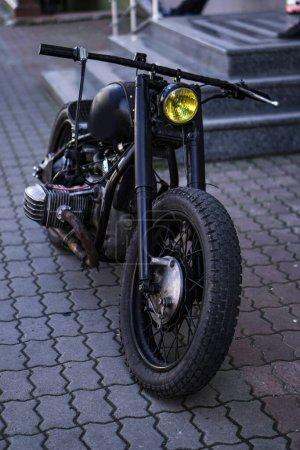 Photo pour Une vieille moto artisanale se dresse dans la rue. Thème punk et motard. Contexte du stock - image libre de droit