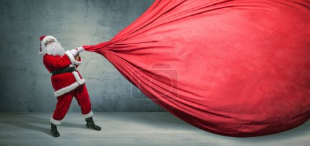 Photo for Santa Claus with big bag on blank advertisement banner with copy space. Christmas theme, sales - Image - Royalty Free Image