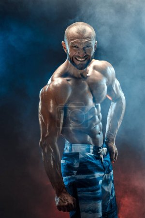 Handsome strong bodybuilder posing in studio on bl...