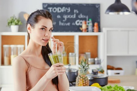 Photo for A young girl drinks a cocktail on a kitchen. - Royalty Free Image