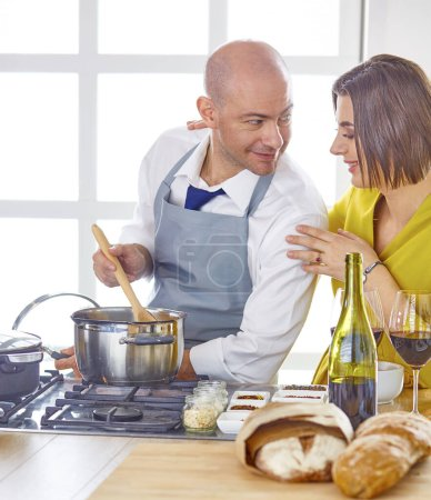 Photo for Couple cooking together in the kitchen at home - Royalty Free Image