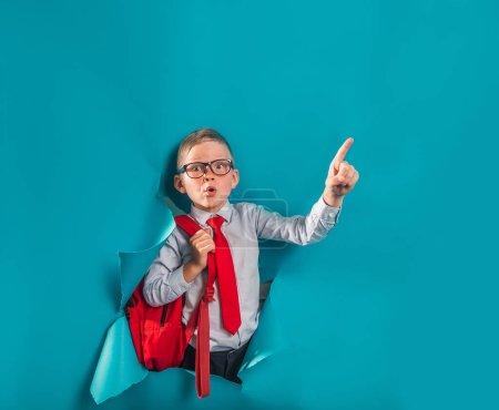 Photo pour Joyeux garçon souriant en uniforme briser mur de papier bleu. Un gamin surpris avec des lunettes retourne à l'école. Succès, motivation, vainqueur, concept de génie. Homme d'affaires regardant à travers le trou dans le mur de papier pointant vers le haut. - image libre de droit