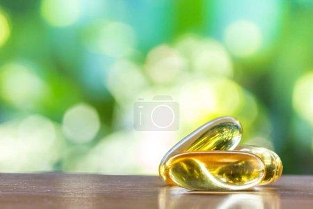 Photo pour Capsules de supplément d'huile de poisson en mise au point sélective sur la table en bois supérieure avec fond bokeh naturel vert - image libre de droit