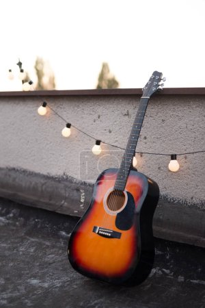 Picture of nice stringed accoustic guitar on rooftop