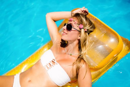 Woman enjoying summer on mattress in swimming pool