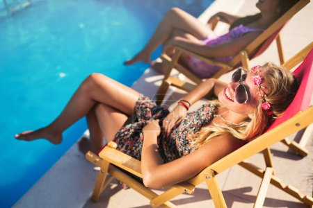 Girls enjoying summer vacation in chairs tanning