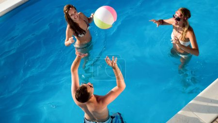 Group of happy people partying in pool