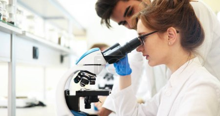 Young female scientist looking through microscope in laboratory